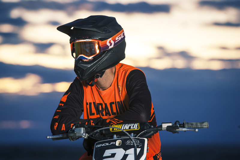 Scott rider on motorcycle wearing an orange kit with the Mojve Prospect goggle with the sunset behing him